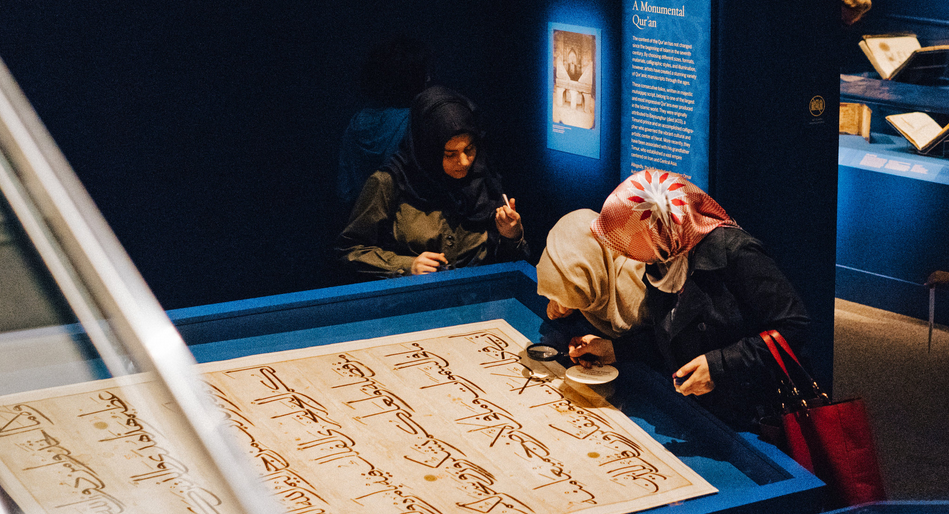 "Visitors studying a folio from a large Quran dating to about 1400 in the exhibition ""The Art of the Qur'an: Treasures From the Museum of Turkish and Islamic Arts,"" at the Arthur M. Sackler Gallery in Washington. Credit Justin T. Gellerson for The New York Times"